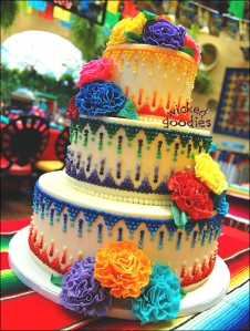 Mexican themed round wedding cake with modeling chocolate carnations and piped buttercream frosting cascading dot design in many colors by Wicked Goodies